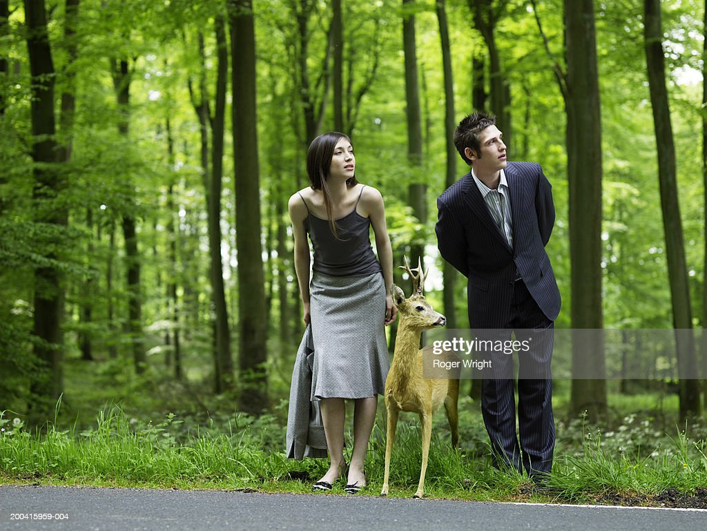 Businessman, woman and stuffed deer looking down country road
