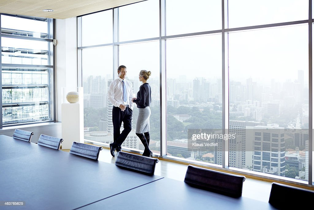 Businessman & woman standing by big windows : Stock Photo