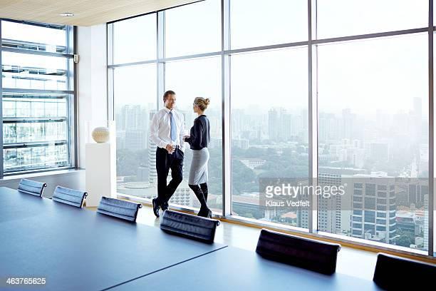Businessman & woman standing by big windows