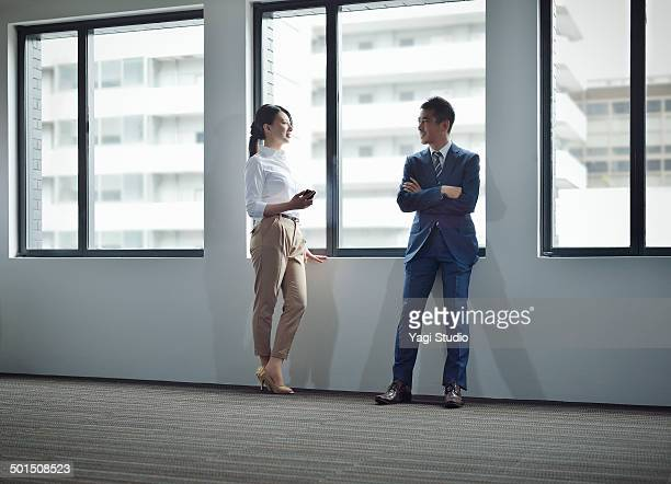 Businessman & woman standing by windows