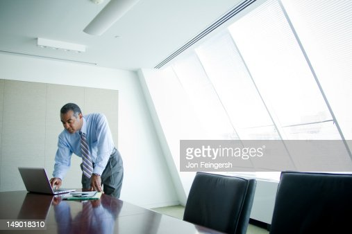 Businessman working alone at board table : Stock Photo