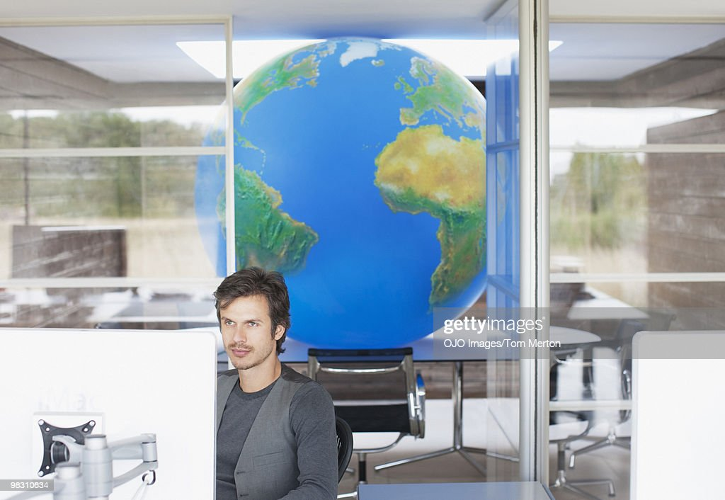 Businessman working at computer with large globe in background : Stock Photo