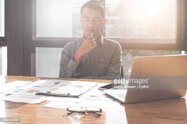 Businessman Working At Desk In Office During Sunset