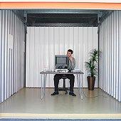 Businessman working at desk in storage unit