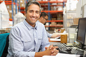 Businessman Working At Desk In Warehouse Smiling To Camera