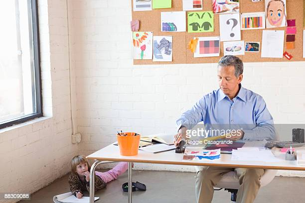 Businessman working at home office with daughter