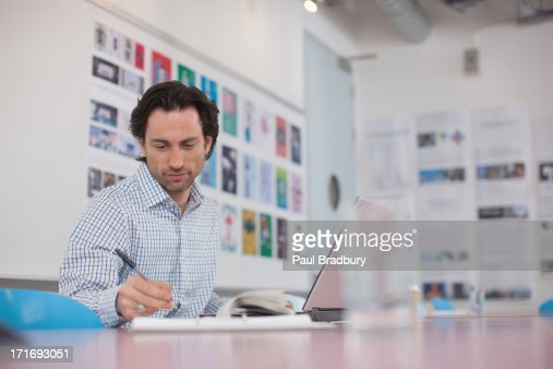 Businessman working at laptop in office : Stock Photo