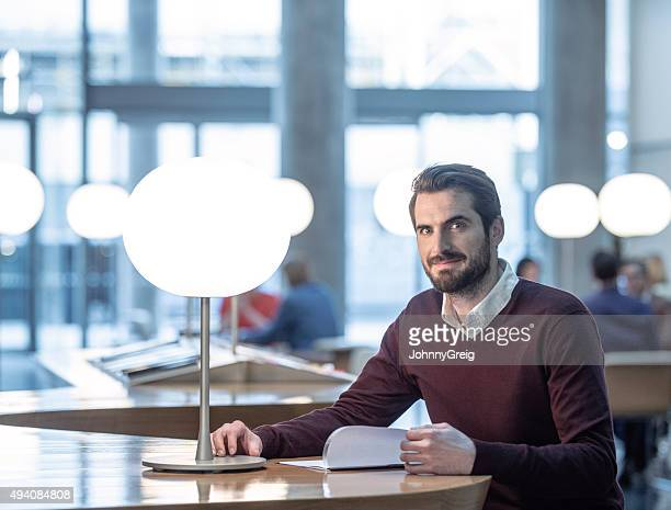 Businessman working by lamp looking at camera, portrait