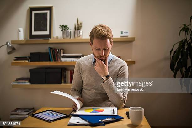 Businessman working from home office analyzing market research statistics