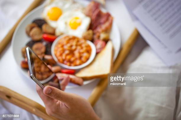 Businessman working in bed and eating  Irish breakfast on tray.