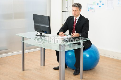 homme daffaires travaillant dans le bureau assis sur la swiss ball photo thinkstock. Black Bedroom Furniture Sets. Home Design Ideas