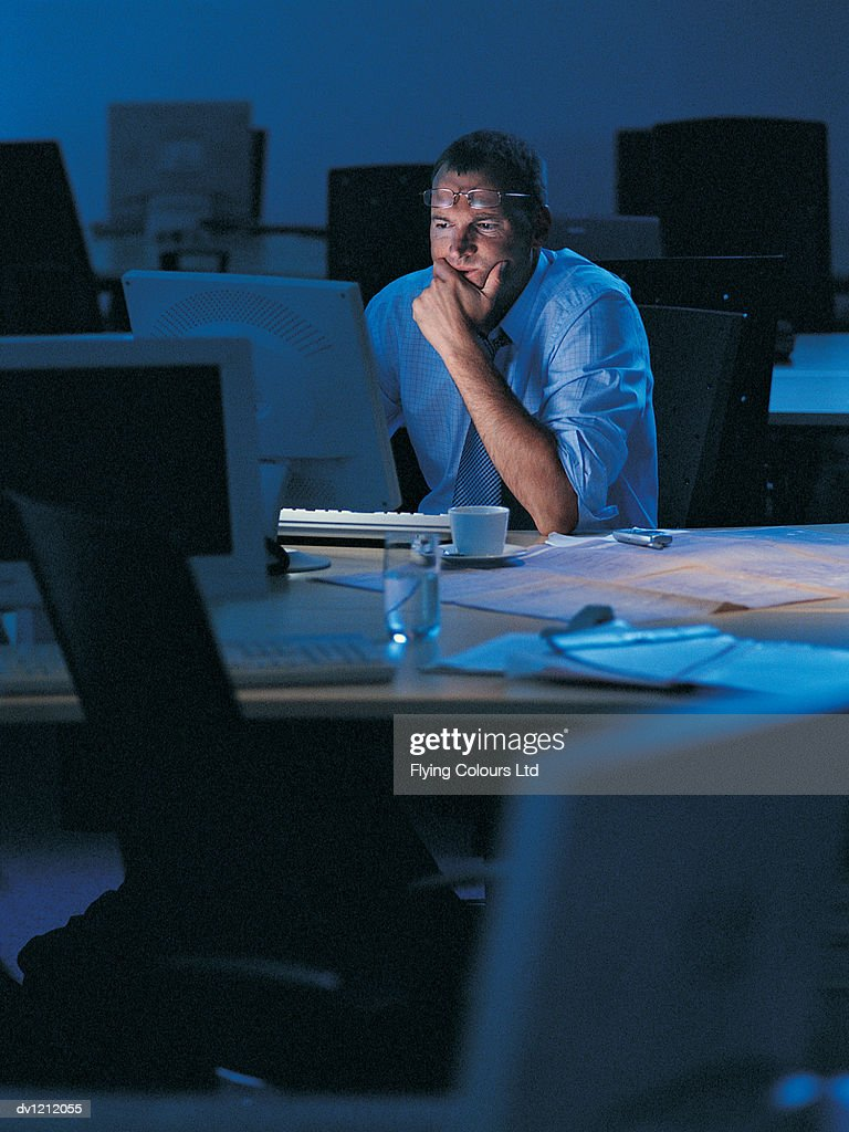 Businessman Working Late in a Dark Office : Stock Photo