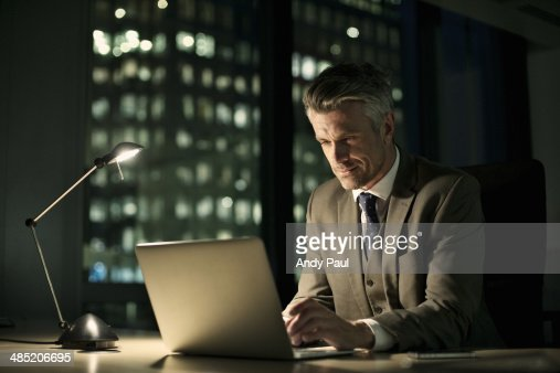 Businessman working late in office on laptop : Stock Photo