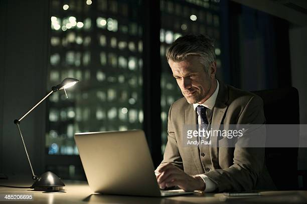 Businessman working late in office on laptop