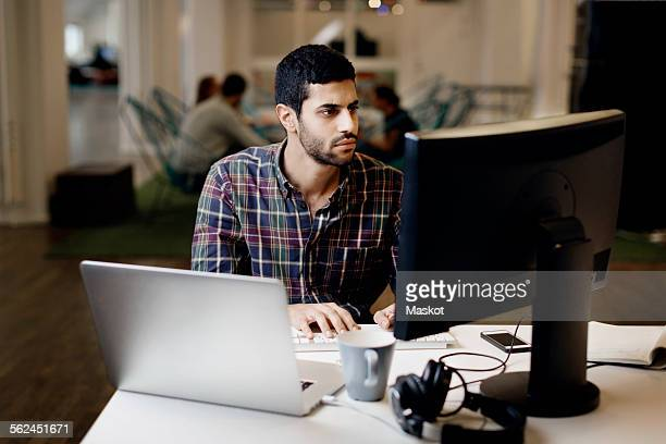 Businessman working late on desktop PC in creative office