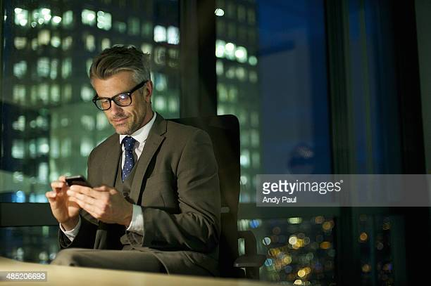 Businessman working late texting on smartphone