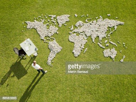 Businessman working near world map made of rocks