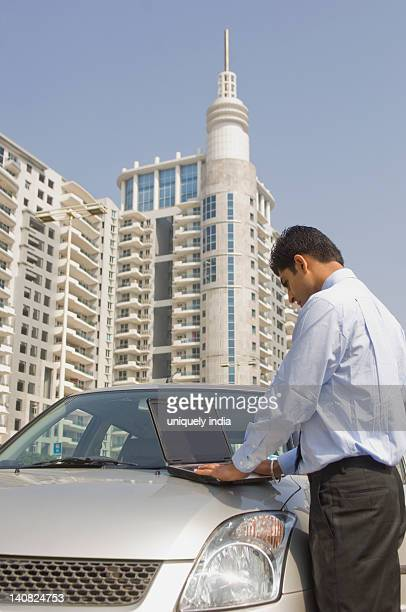 Businessman working on a laptop on a car hood, Gurgaon, Haryana, India