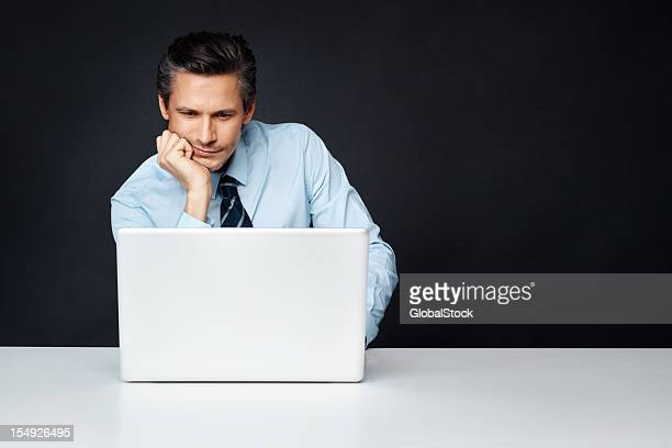Businessman working on a laptop on a white table