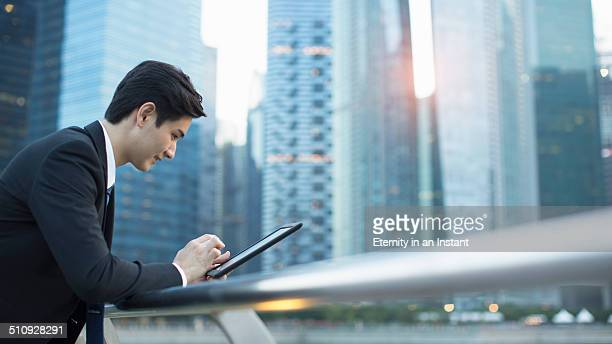 Businessman working on a tablet in the city.