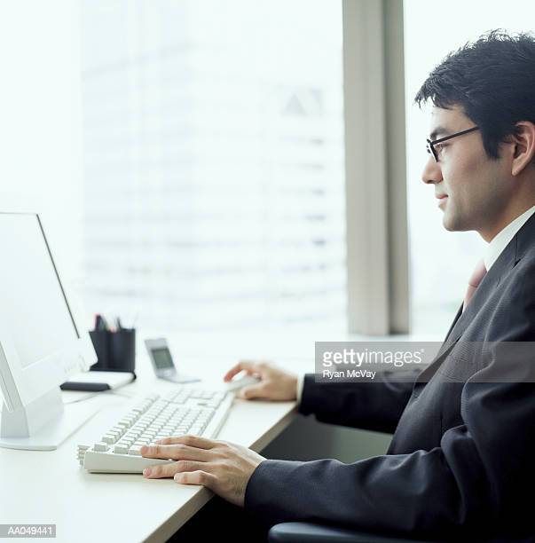 Businessman working on computer at desk in office, side view