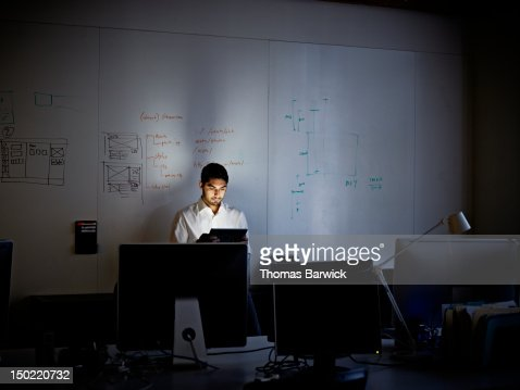 Businessman working on digital tablet at night : Stock Photo