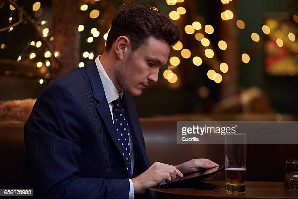 Businessman Working On Digital Tablet In Bar After Work