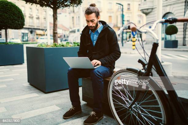Businessman working on laptop and drinking coffee outdoors