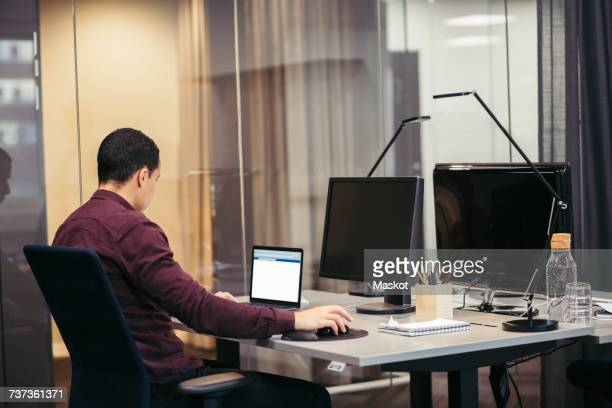 Businessman working on laptop at desk in office