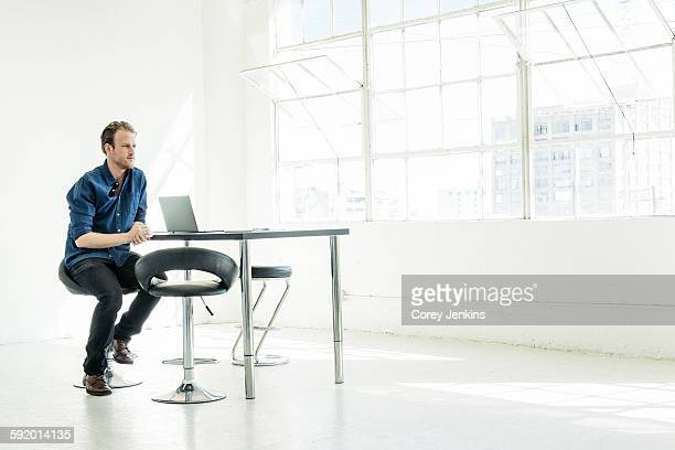 Businessman working on laptop by office window