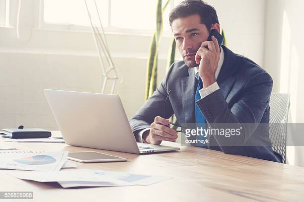 Businessman working on laptop computer and mobile phone.