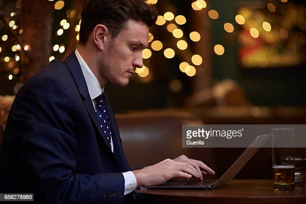 Businessman Working On Laptop In Bar After Work