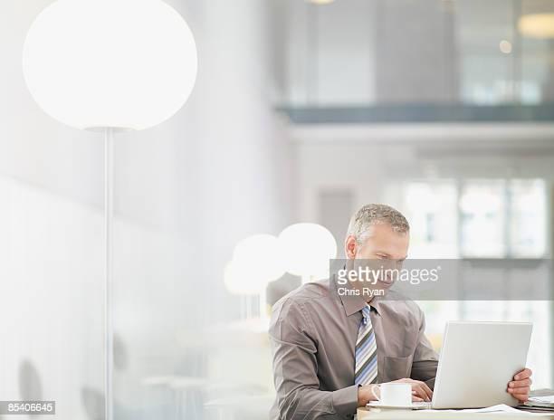 Empresário trabalhando no computador portátil no Café