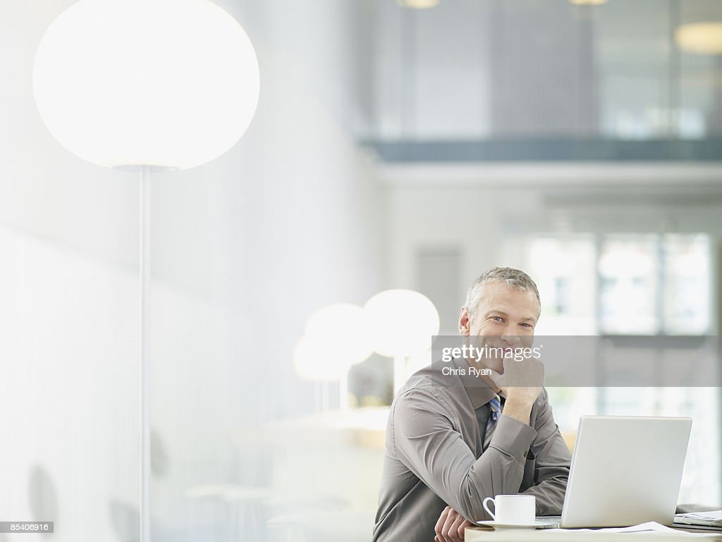Businessman working on laptop in cafe : Stock Photo