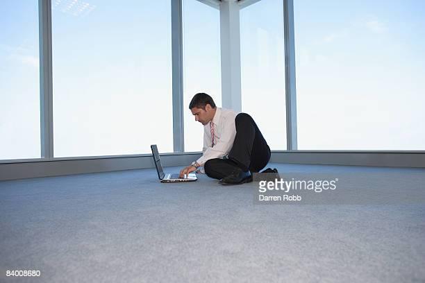Businessman working on laptop in empty office