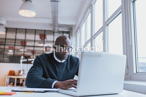 Businessman working on laptop in office : Stock Photo