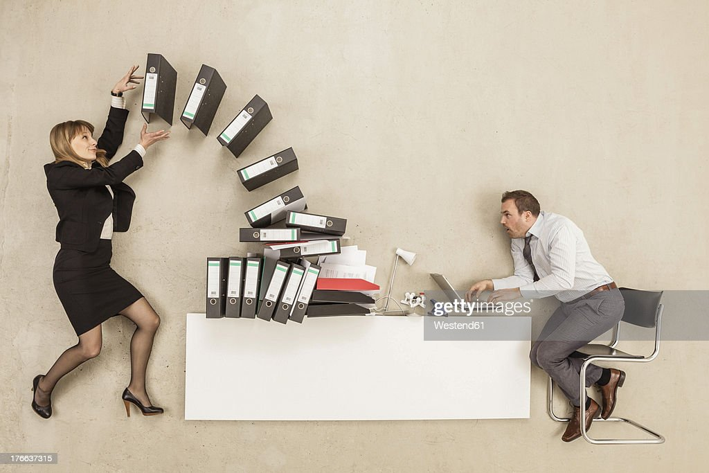 Businessman working on office desk while businesswoman providing stack of files : Foto de stock