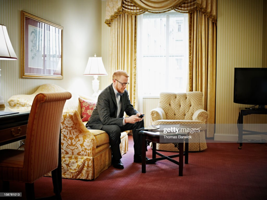 Businessman working on smartphone in hotel : Stock Photo
