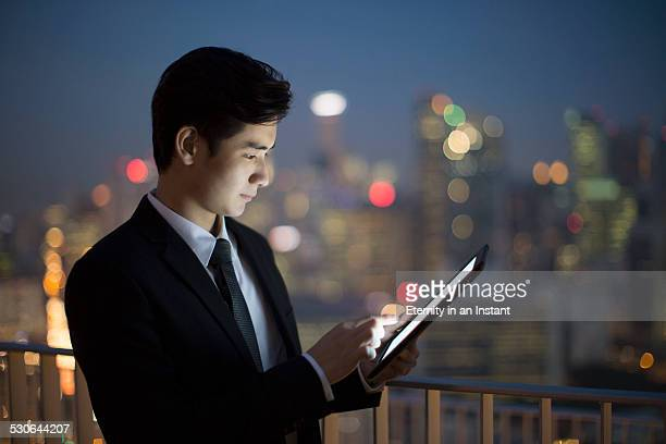 Businessman working on tablet at night
