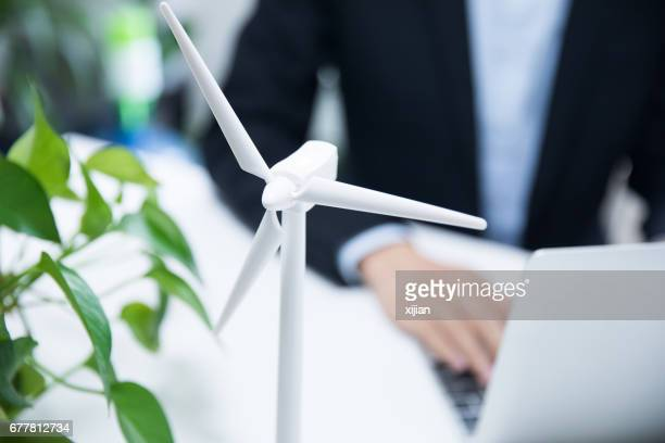 Businessman working with model wind turbines