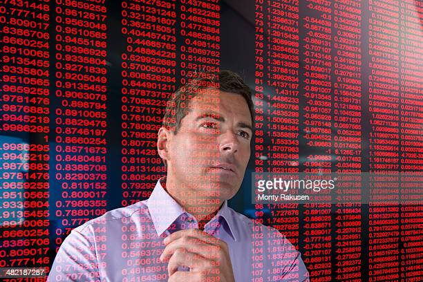 Businessman working with red figures seen through screen