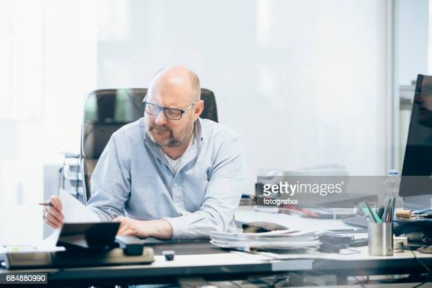 businessman works at desk in office, looking into document