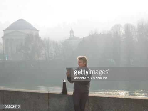 Businessman works on digital tablet above river : Stock Photo