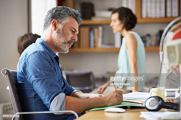 Businessman writing at desk in office
