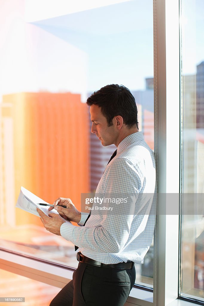 Businessman writing at window in office : Stock Photo