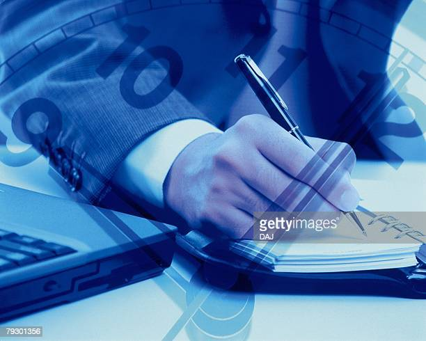 Businessman writing down on personal organizer and image of clock, CG, composition, toned image