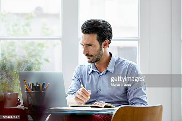 Businessman writing notes while using laptop