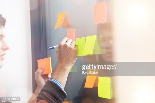 Businessman writing on a sticky note. : Stock Photo
