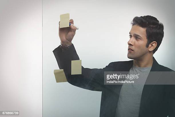 Businessman writing on adhesive notes in office