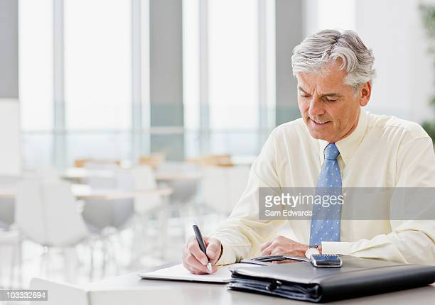 Businessman writing on notepad in cafeteria